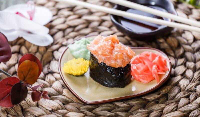 Maki Gunkan σουσιών με το σολομό στο πιάτο στο χαλί μπαμπού που διακοσμείται με τα λουλούδια Ιαπωνική κουζίνα στοκ εικόνα με δικαίωμα ελεύθερης χρήσης