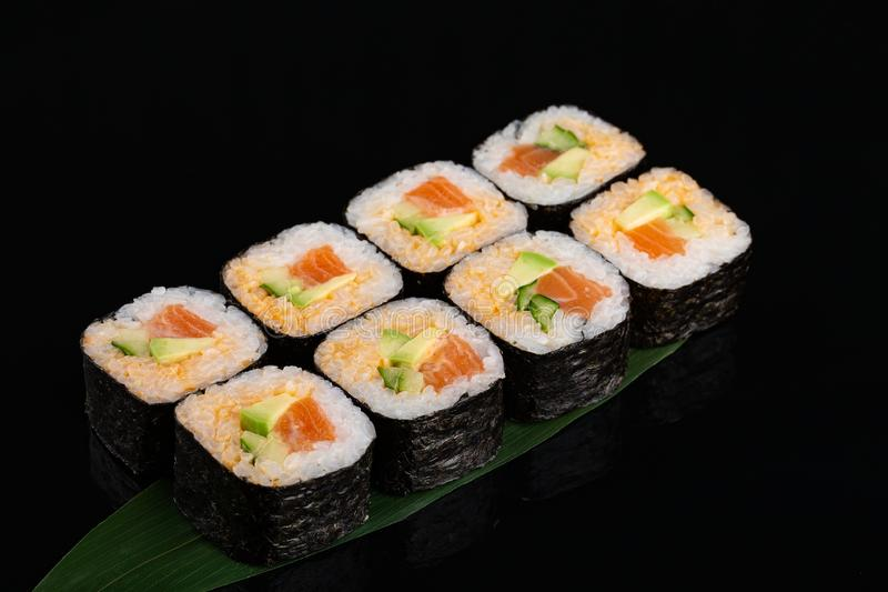 Maki sushi with avocado, cucumber and salmon on banana leaf stock images