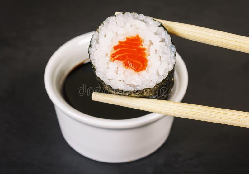 Maki-Sushi mit Essstäbchen- und Sojasoßennahaufnahme stockbilder