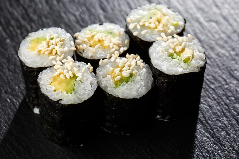 Maki Sushi Rolls with cucumber or avocado on black stone on dark background. Sushi menu. Japanese food. Closeup of delicious royalty free stock images