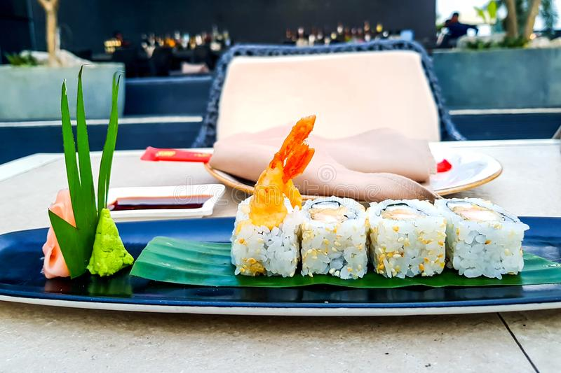 Maki sushi rolls with giant tempura prawns on a plate with wasabi stock image
