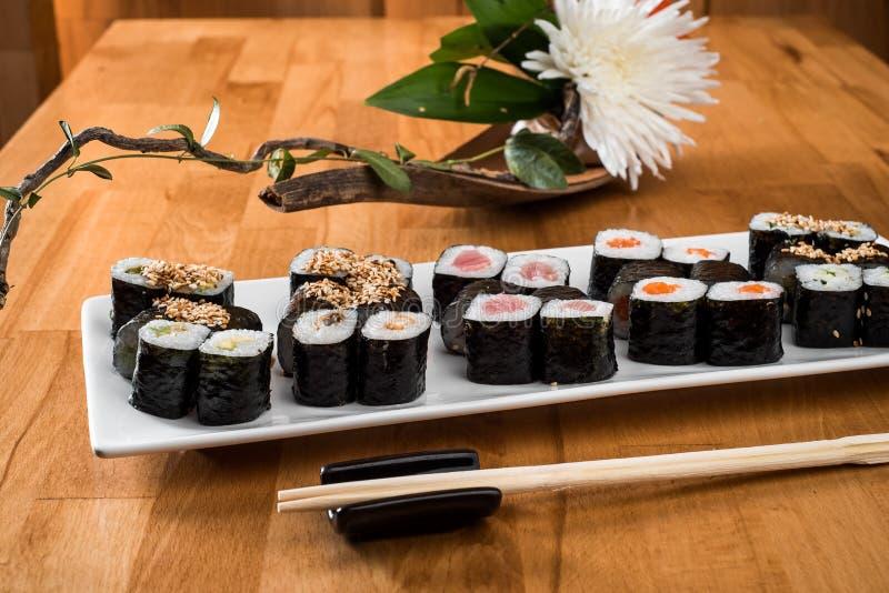 Maki Sushi roule avec les saumons, le thon, l'anguille et l'avocat sur un plat blanc Fin vers le haut photographie stock libre de droits