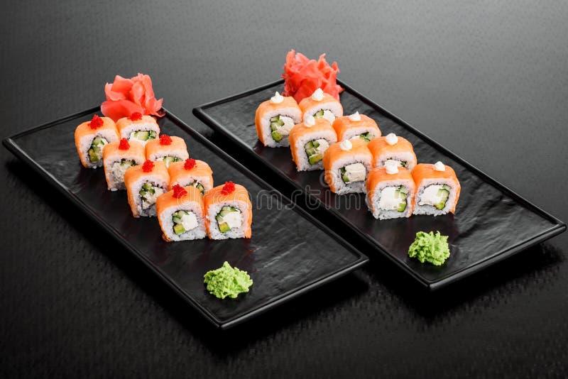 Maki Sushi stellte auf dunklen Musterhintergrund ein Gesetztes nigiri, Rollen und Sashimi der Sushi dienten in der schwarzen quad stockbilder