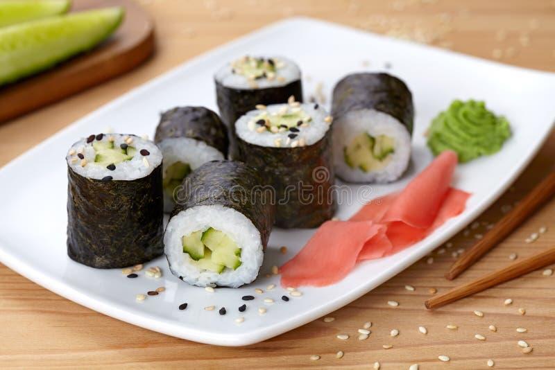 Maki sushirulle med gurkan, wasabi, ingefära och arkivbild