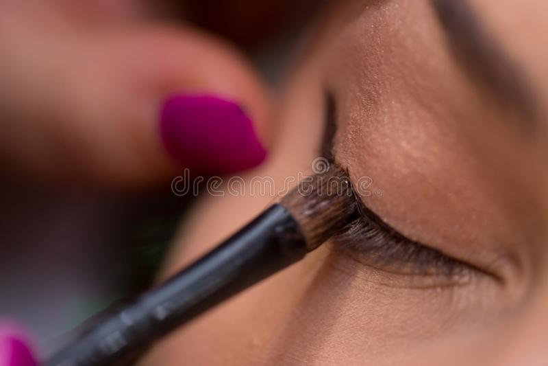 Makijażu artysta stawia oko liniowa na kobiety oku w salonie zdjęcia stock