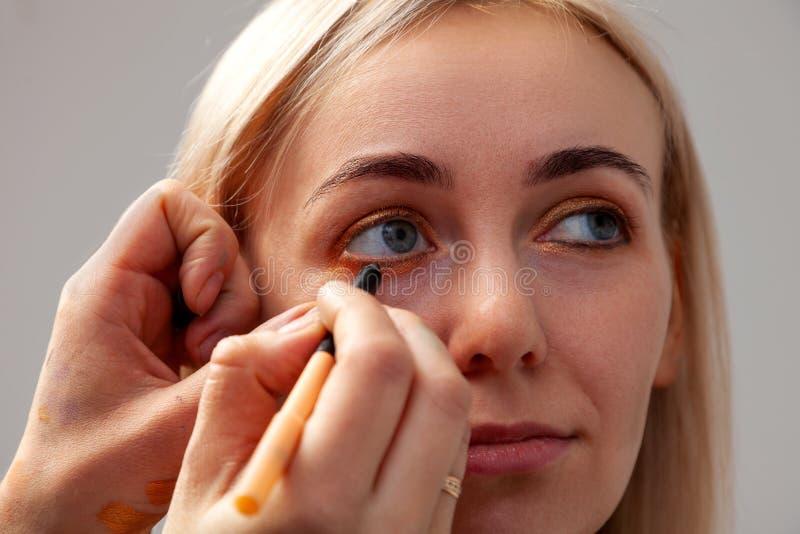 Makijażu artysta z pomocą ołówka w jeden ręce rysuje strzałę na rozpieczętowanych oczach model z innymi ręk ciągnieniami, zdjęcie royalty free