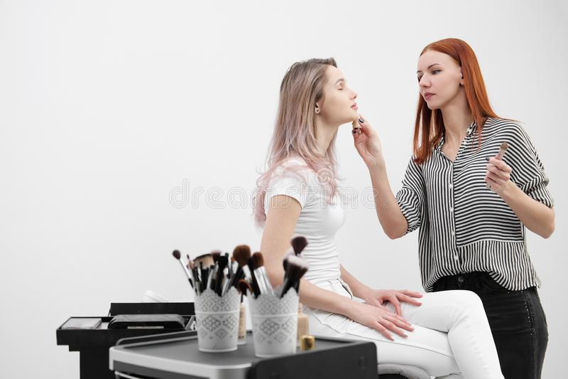 Makijażu artysty rudzielec dziewczyna robi makeup pięknej blondynki kobiety modelować na białym tle Obok fury z narzędziami obrazy royalty free
