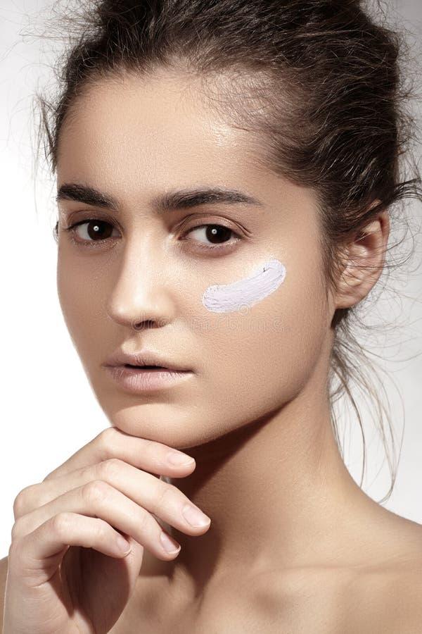 Makijaż & kosmetyki. Piękny model z czystą skórą, fundacyjna concealer śmietanka zdjęcie royalty free