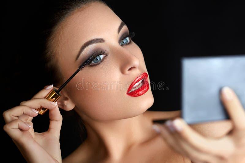 Makijaż Piękna kobieta robi makeup Tusz do rzęs muśnięcie czerwone usta obraz royalty free