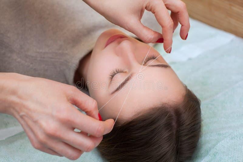 Makijażu artysta koryguje makeup, daje kształtowi i nić skuba brwi w piękno salonie zdjęcie stock