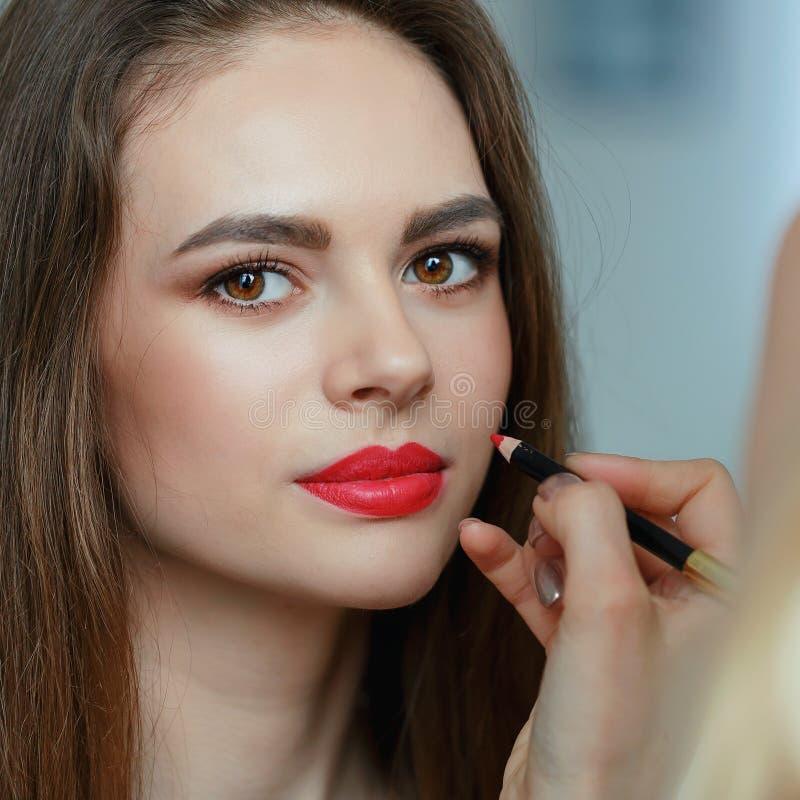 Makijażu artysta maluje wargi na wzorcowej twarzy obraz stock
