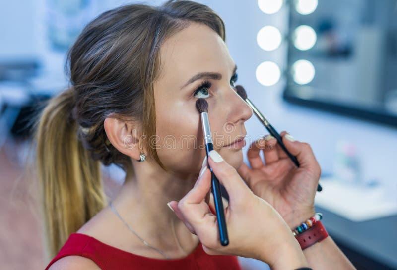 Makijażu artysta robi dymiącemu oka makeup piękna młoda dziewczyna obraz stock