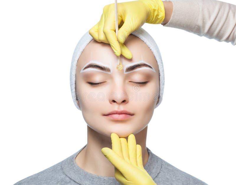 Makijażu artysta skuba jej brwi, przed procedurą stały makijaż obraz royalty free
