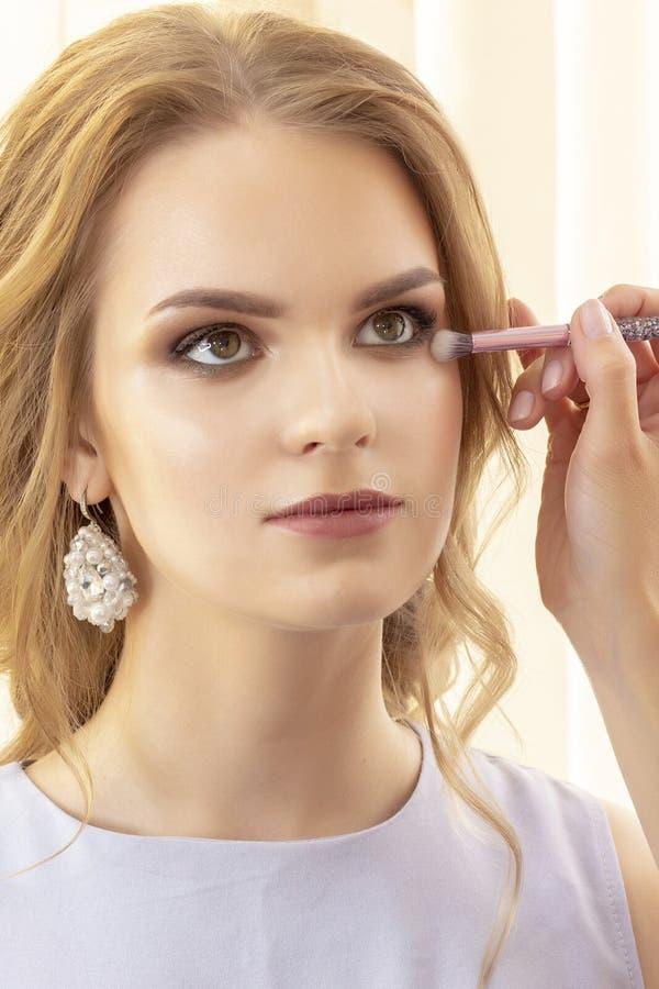 Makijażu artysta stosuje pięknych modelów cień i concealer na twarzy pionowo fotografii i powiekach zdjęcia royalty free