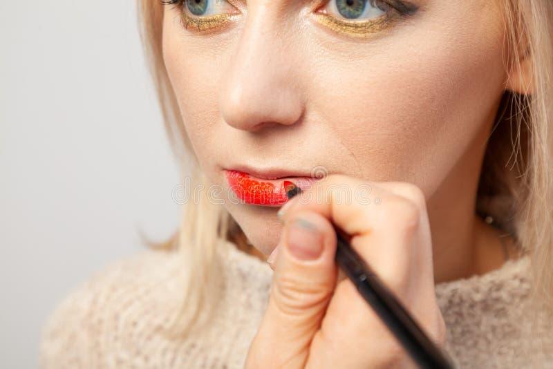 Makijażu artysta w studiu narzuca luksusowego orientalnego makijaż młodej dziewczyny blondynka, w czyj ręce muśnięcie trzyma obraz royalty free