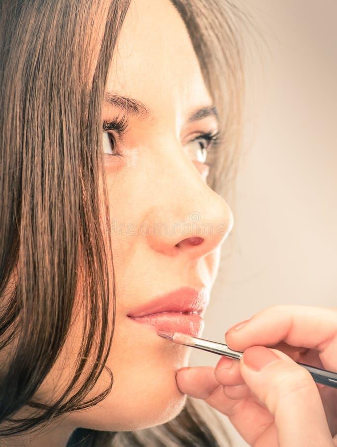 Makijażu artysty fryszowania wargi piękni potomstwa Modelują obraz stock