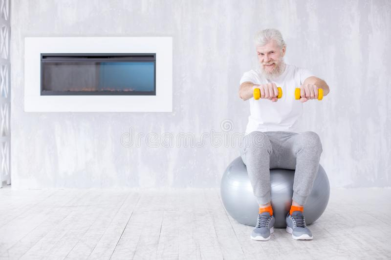 Cheerful senior man sitting on yoga ball and holding dumbbells royalty free stock photos