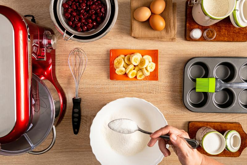 Making batter procedure and other ingredients for muffin making. White bowl with flour and a spoon full of sugar, stand mixer,hand whisk, strained cherries stock image
