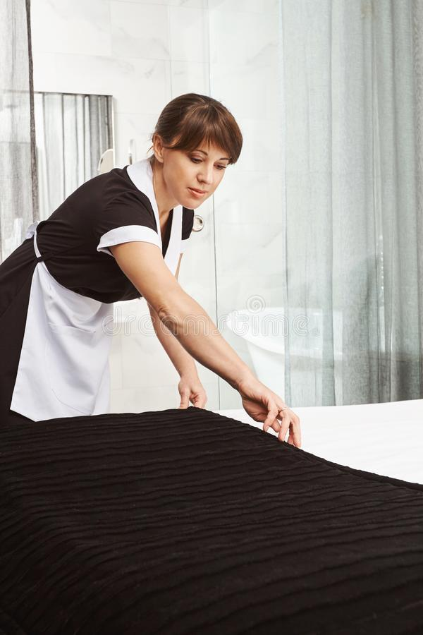 Making bed is like art. Indoor shot of maid in uniform, putting blanket on bed while cleaning hotel apartment or house stock photo