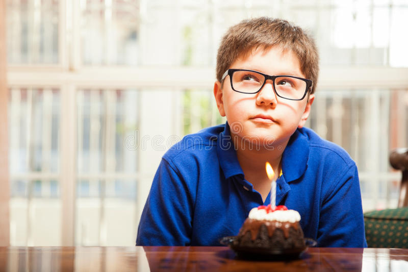Making a birthday wish. Kid with glasses thinking of a birthday wish before blowing out a candle royalty free stock photography