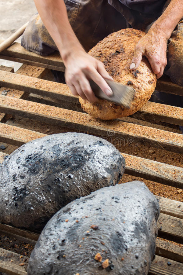 Making bread the traditional way - cleaning away the charred crust. Making bread the traditional way - cleaning the charred crust from an oven baked bread royalty free stock image