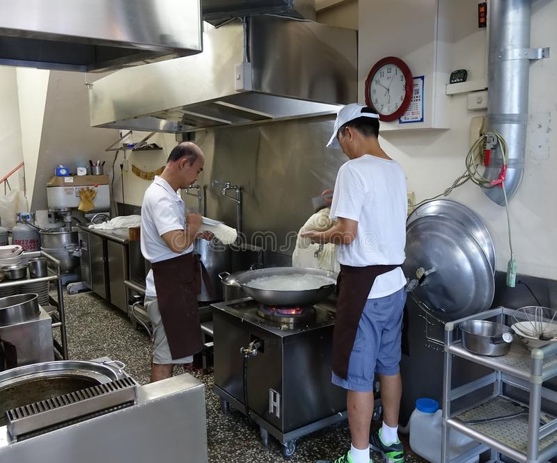 Making Chinese Knife-Cut Noodles. KAOHSIUNG, TAIWAN -- JULY 24, 2016: Two cooks prepare knife-cut noodles, a traditional dish from north-western China stock image