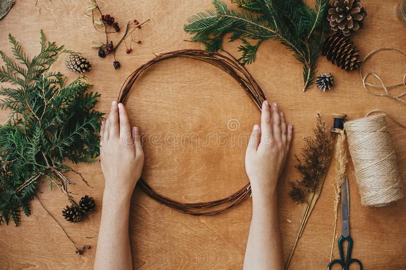 Making christmas wreath. Hands holding wooden circle and fir branches, pine cones, thread, scissors, herbs on wooden table. Details for workshop of making stock photo