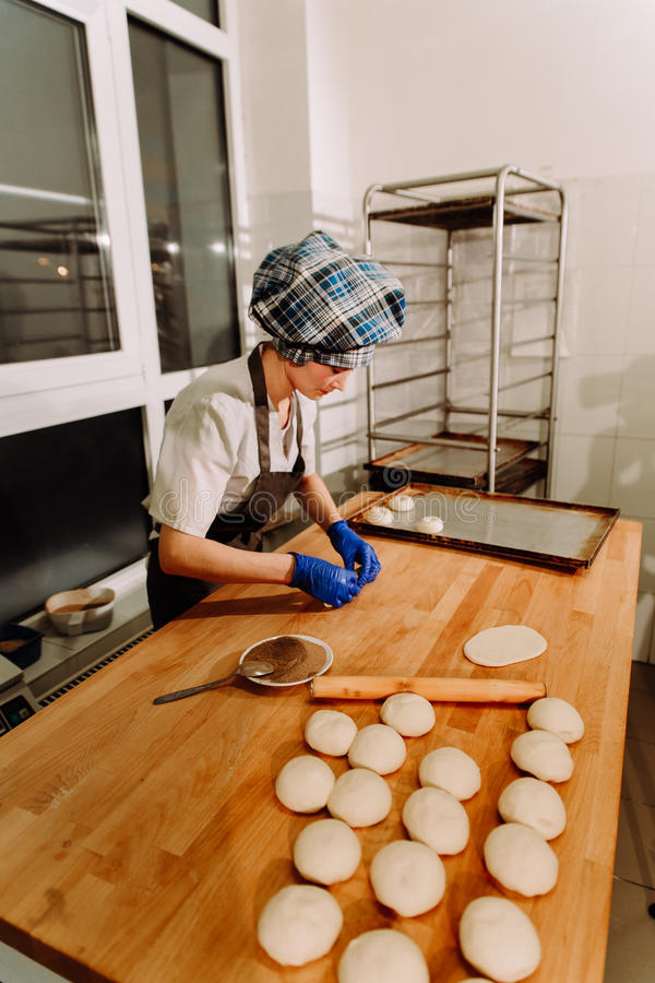 Making cinnamon buns. Homemade raw yeast dough after raising ready to bake. A Baker making cinnamon rolls royalty free stock photos
