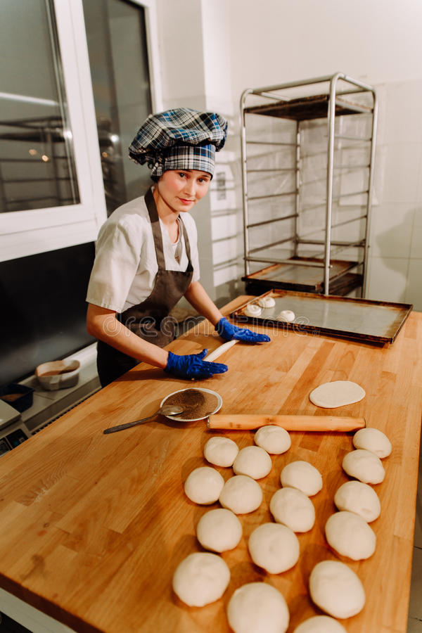 Making cinnamon buns. Homemade raw yeast dough after raising ready to bake. A Baker making cinnamon rolls royalty free stock image