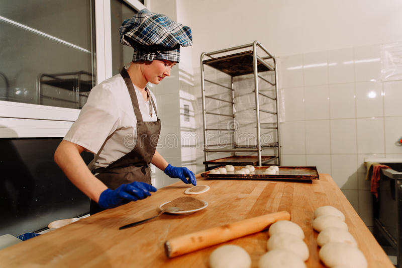Making cinnamon buns. Homemade raw yeast dough after raising ready to bake. A Baker making cinnamon rolls stock photography