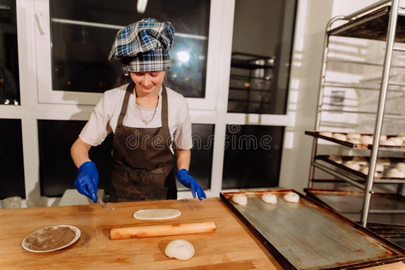 Making cinnamon buns. Homemade raw yeast dough after raising ready to bake. A Baker making cinnamon rolls stock photo