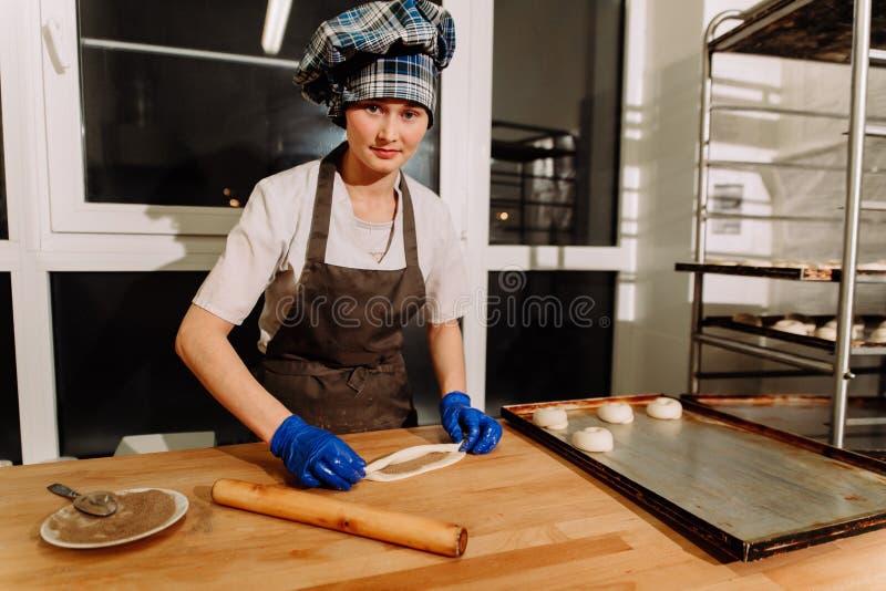 Making cinnamon buns. Homemade raw yeast dough after raising ready to bake. A Baker making cinnamon rolls stock image