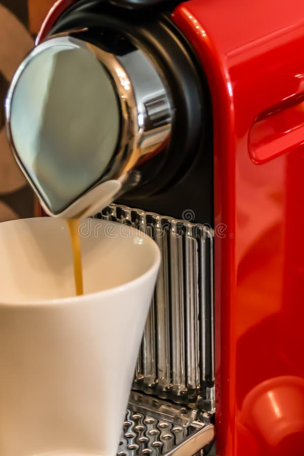 Making coffee: close-up of a red cup-based coffee machine, pouring coffee. In a white mug stock images