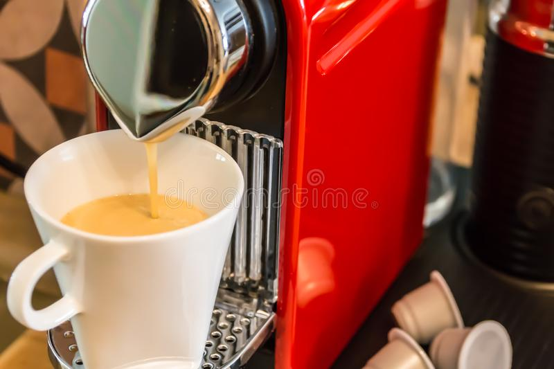 Making coffee: close-up of a red cup-based coffee machine, pouring coffee. In a white mug stock image