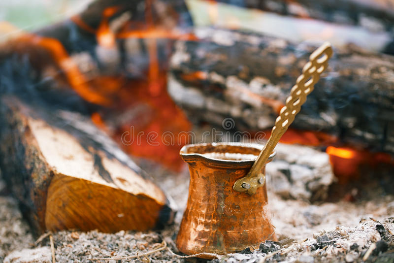 Making coffee in the fireplace when camping or hiking stock photo