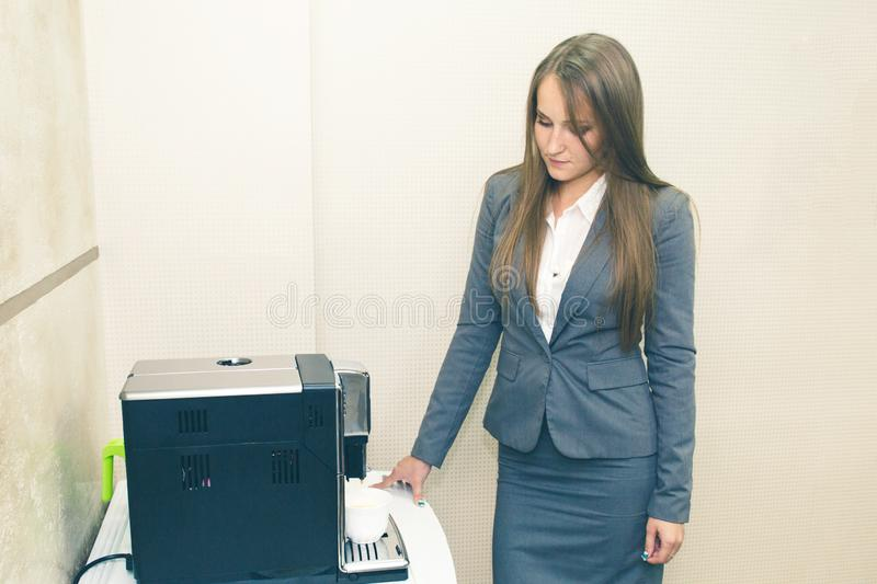 Making coffee. Making coffee in the office in the coffee machine. A girl in a suit prepares coffee for colleagues. royalty free stock image