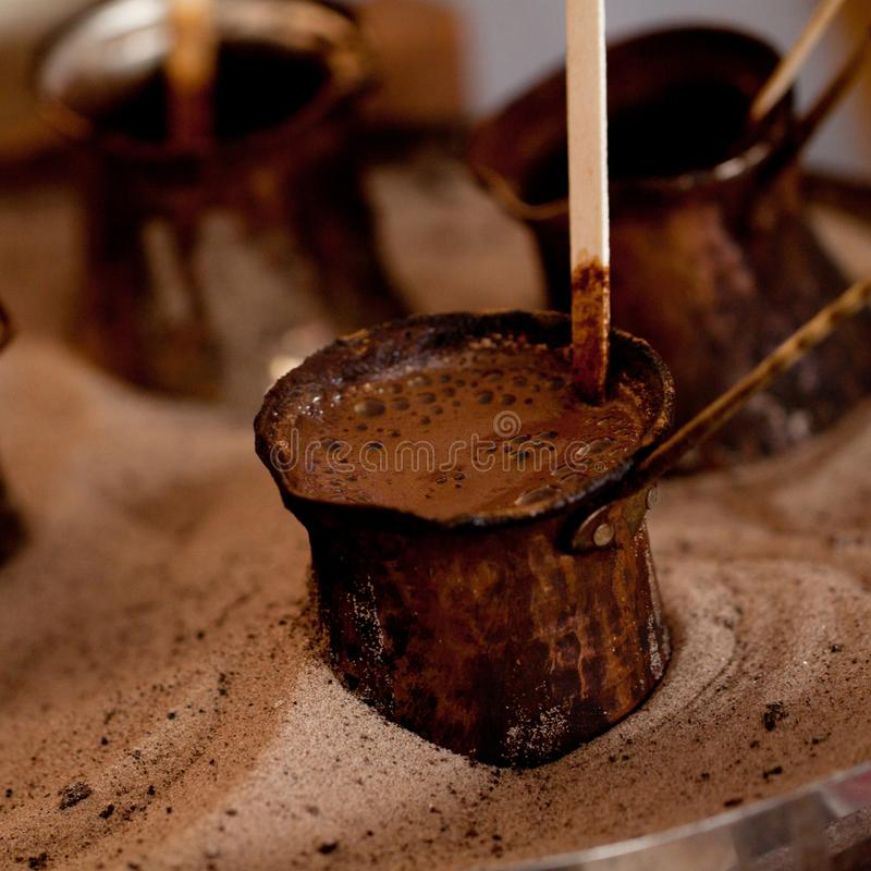 Making coffee in the sand. In a cafe or restaurant natural coffee is brewed in copper turks in the sand stock images