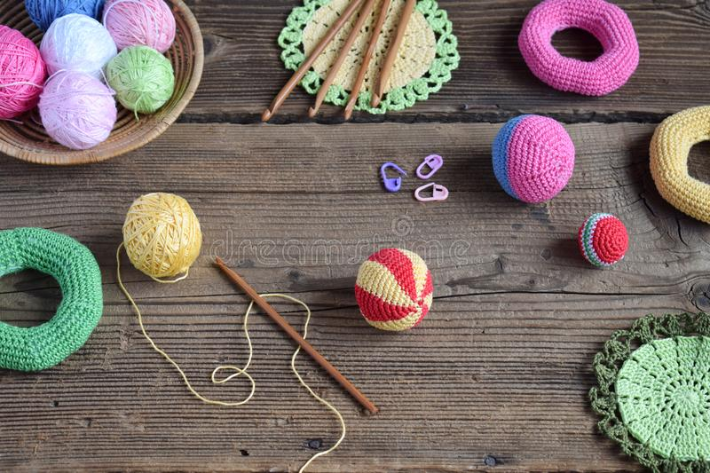 Making colored crochet balls. Toy for babies and toddlers to learn mechanical skills and colors. On the table threads, needles,. Hook, cotton yarn. Handmade stock images