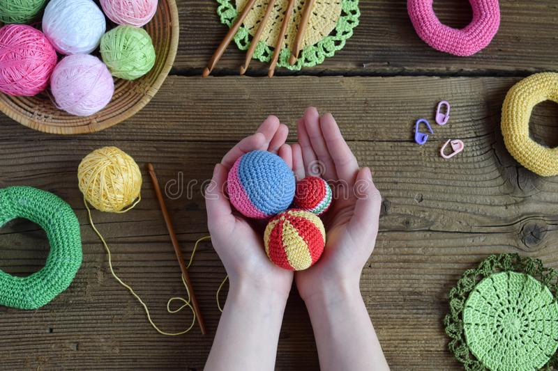 Making colored crochet balls. Toy for babies and toddlers to learn mechanical skills and colors. On the table threads, needles,. Hook, cotton yarn. Handmade royalty free stock photos