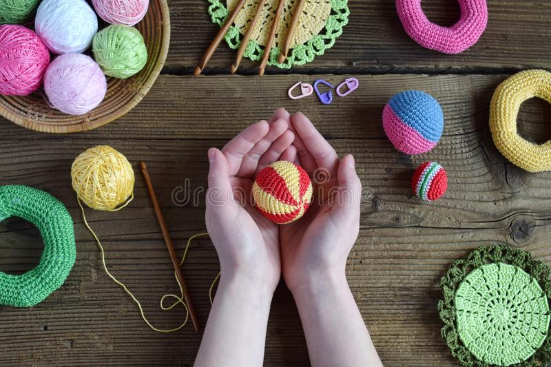 Making colored crochet balls. Toy for babies and toddlers to learn mechanical skills and colors. On the table threads, needles,. Hook, cotton yarn. Handmade stock photography