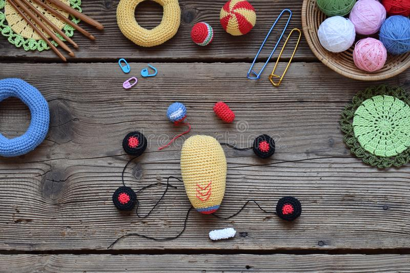 Making colored crochet racing car. Toy for babies and toddlers to learn mechanical skills and colors. On the table threads,. Needles, hook, cotton yarn stock images