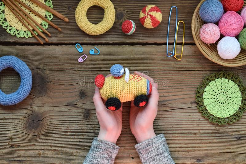 Making colored crochet racing car. Toy for babies and toddlers to learn mechanical skills and colors. On the table threads,. Needles, hook, cotton yarn stock photo