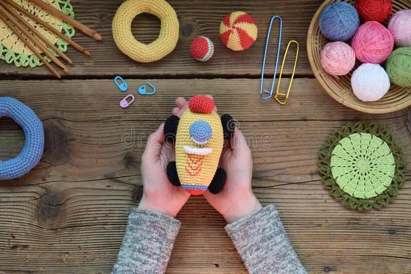 Making colored crochet racing car. Toy for babies and toddlers to learn mechanical skills and colors. On the table threads,. Needles, hook, cotton yarn royalty free stock photography