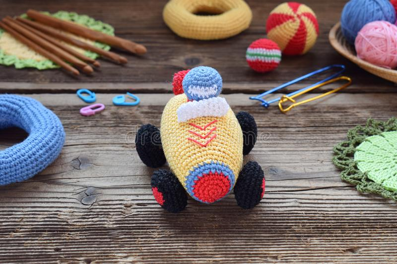 Making colored crochet racing car. Toy for babies and toddlers to learn mechanical skills and colors. On the table threads,. Needles, hook, cotton yarn royalty free stock image