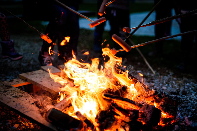 Making and cooking Hot dog sausages over open camp fire. stock image