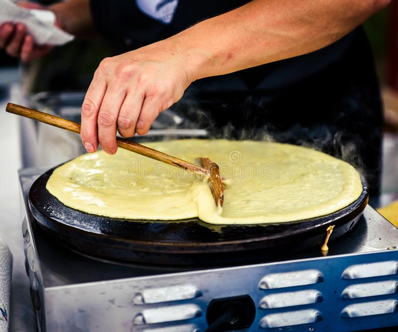 Making of crepes pancakes in open market festival fair. stock photo