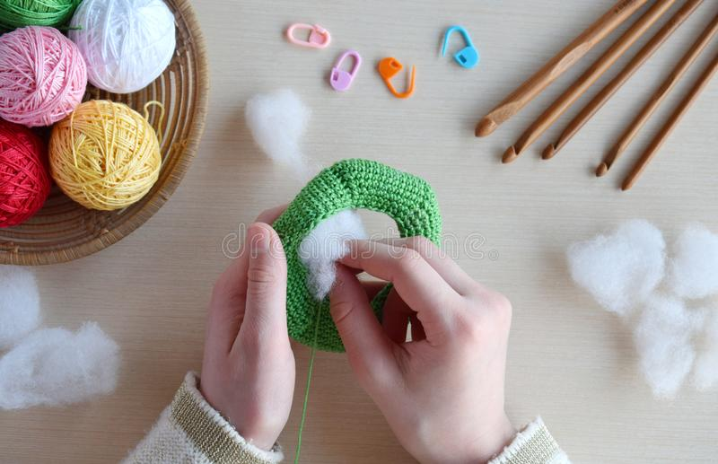 Making crochet pyramid from colored rings. Toy for babies and toddlers to learn mechanical skills and colors. On the table threads. Needles, hook, cotton yarn royalty free stock photos