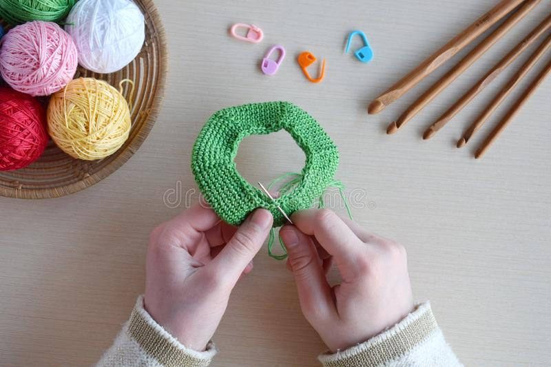Making crochet pyramid from colored rings. Toy for babies and toddlers to learn mechanical skills and colors. On the table threads. Needles, hook, cotton yarn stock photos