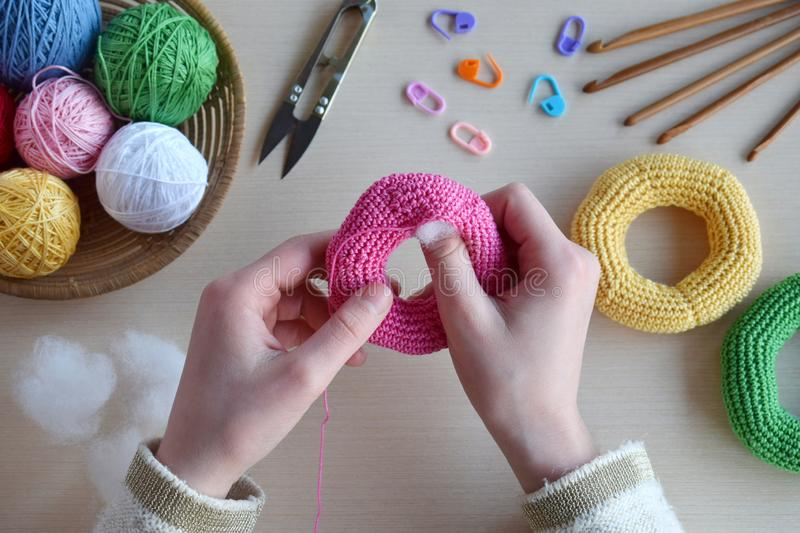 Making crochet pyramid from colored rings. Toy for babies and toddlers to learn mechanical skills and colors. On the table threads. Needles, hook, cotton yarn stock image