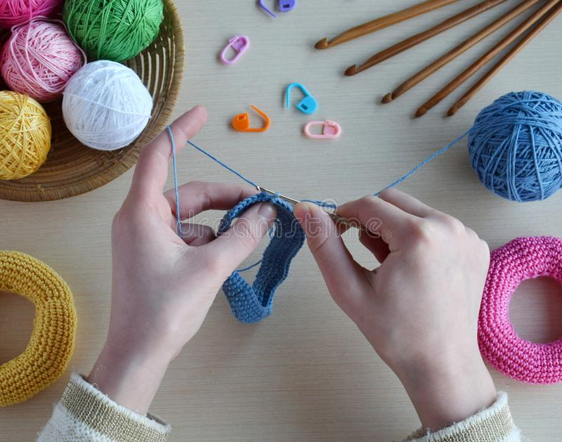 Making crochet pyramid from colored rings. Toy for babies and toddlers to learn mechanical skills and colors. On the table threads. Needles, hook, cotton yarn stock photography